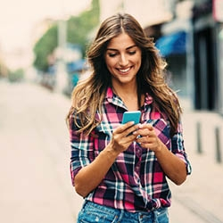 Woman walking while looking at her phone